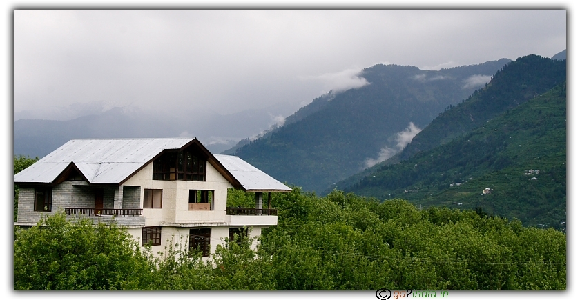 Ice peaks, clouds, green land and house at Khakhnal, Manali