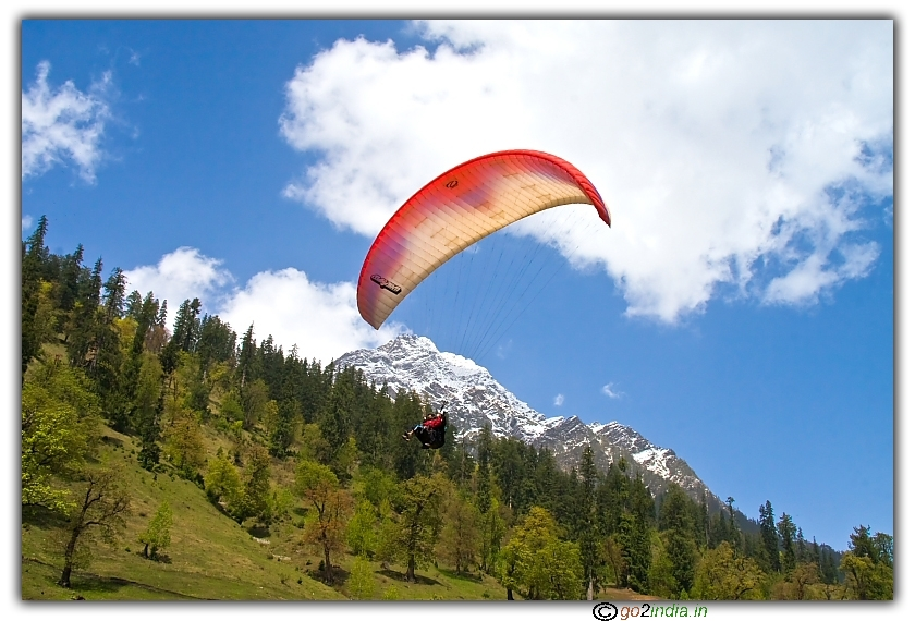 Paragliding over snow covered peaks at Solang valley of Manali