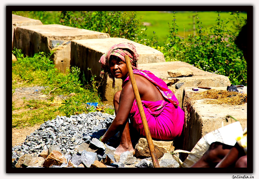 a lady sitting and breaking the pebbles for her daily earnings